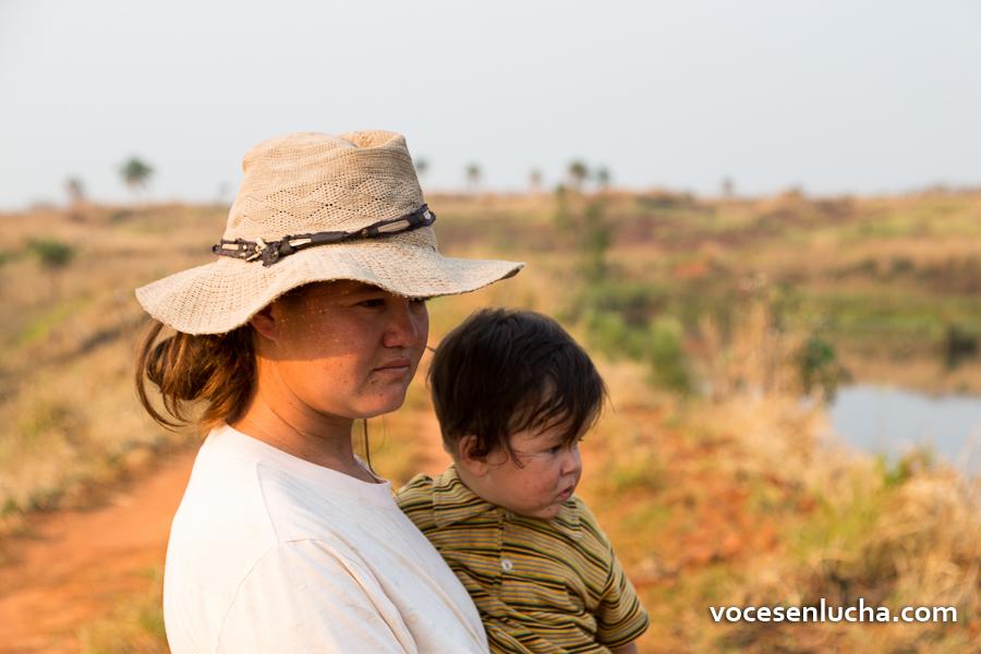 Fotografía de mamá con hijo en brazos en la ocupación de tierras de Marina Kue, en Curuguaty, Paraguay. ENLACE A PARAGUAY
